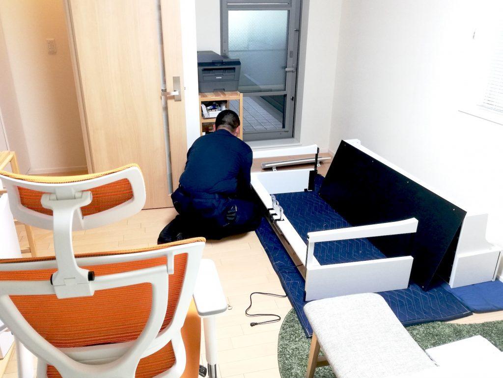 ワンルームでピアノを組み立てている様子